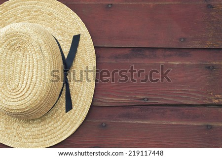 An Amish man's straw hat hangs on a red, wooden barn door - stock photo