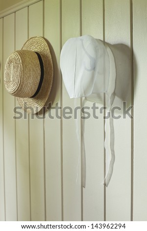 An Amish woman's bonnet and a man's straw hat hanging on a wall - stock photo