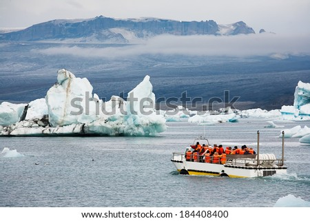 An amphibious vehicle taking tourists for a cruise around the icebergs in the Jokulsarlon glacier lake, where huge chunks of ice from the Vatnajokull glacier float out to the Atlantic ocean  - stock photo
