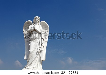 An ancient angel guardian against a blue sky. - stock photo