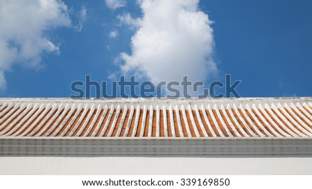 An ancient blank Chinese wall against a blue cloudy sky. - stock photo