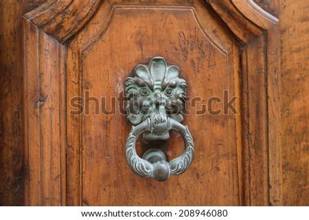 An ancient bronze detail on the old medieval door. A doorknob  - stock photo