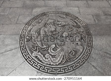 An ancient Chinese imperial dragon and phoenix feng shui symbol on a medieval castle fortress wall. - stock photo