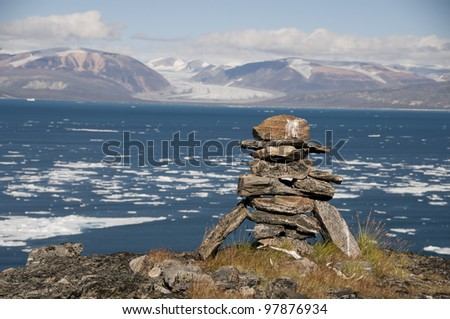 An ancient Inuit inukshuk serves as a landmark for seafarers in a fjord of Baffin Island, Nunavut, Canada.  This inukshuk is estimated to be at least one thousand years old. - stock photo