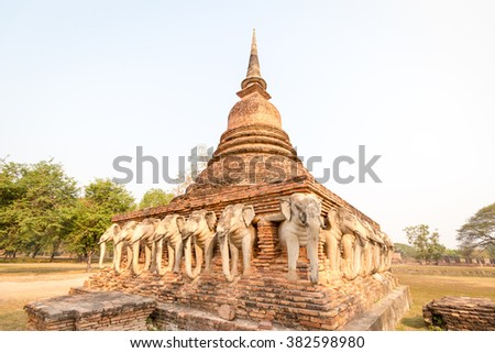 An ancient laterite/sandstone pagoda in Sukhothai's UNESCO world heritage historical park with elephant sculptures all around the four sides. The place is public property, no release document required - stock photo