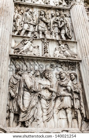 an ancient roman bas-relief located on a paned of the Arch of Trajan. The Arch of Trajan is an ancient Roman triumphal arch in Benevento, southern Italy. - stock photo