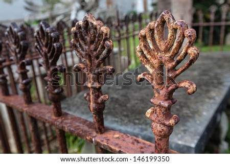 An ancient rusty iron fence surrounding a graveyard tomb. - stock photo