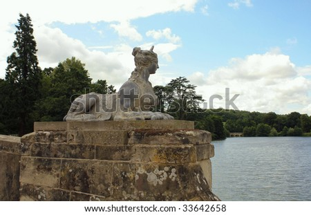 An ancient Sphinx figurine looks out over the lake
