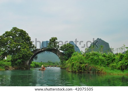 An ancient stone arch bridge over YuLong River, in South China. - stock photo