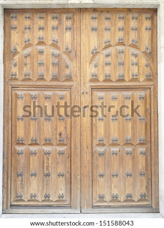An ancient wooden door with rusty nails