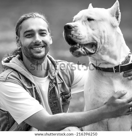 an and Dogo Argentino walk in the park. - stock photo