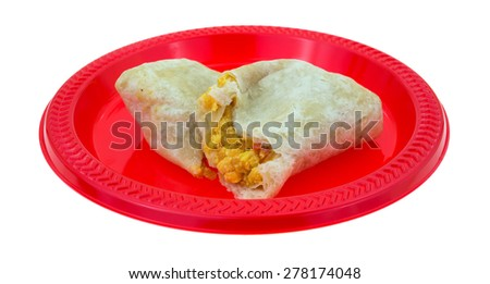 An angle view of a split breakfast burrito on a red plate. - stock photo