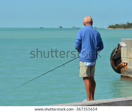 An angler fishing from a concrete seawall. - stock photo