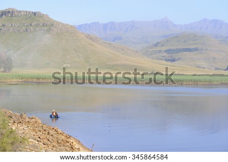 An angler fishing the margins at Giant's Cup Wilderness Reserve, southern Drakensberg, Kwazulu Natal, South Africa - stock photo