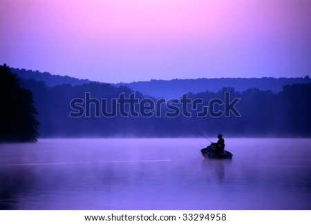 An angler spends a quiet morning on the lake fishing for bass.
