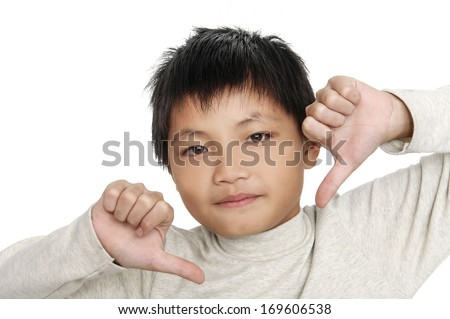 An angry boy is holding his thumb down; isolated on the white background - stock photo