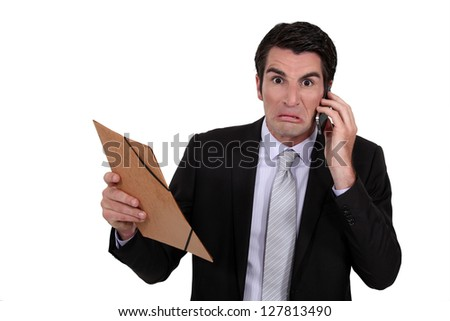An angry businessman over the phone. - stock photo