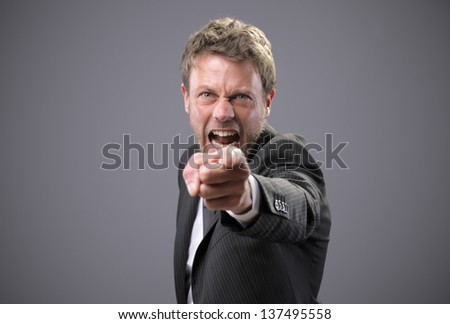 An angry businessman points at the camera