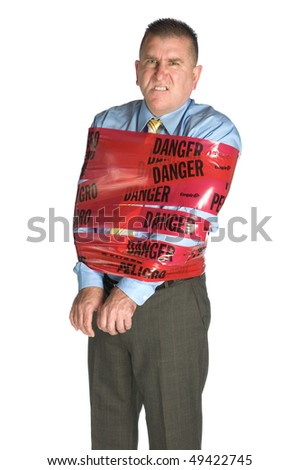 An angry businessman wrapped in danger tape as a warning to coworkers snarls as a result of stress and frustration - stock photo