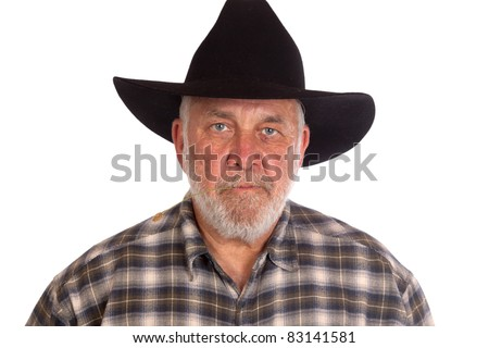 An angry cowboy has a piece of straw in his mouth.  He is wearing a black cowboy hat.
