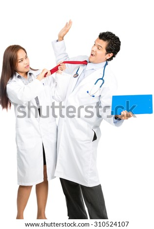 An angry female Asian doctor physically attacks hispanic male colleague, frustrated, pulling his tie, him scared, recoiling and surrendering in exaggerated terror. Vertical
