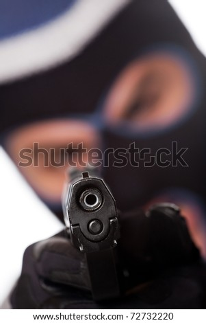 An angry looking man wearing a ski mask pointing a black handgun at the viewer. Shallow depth of field.