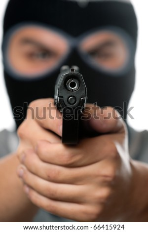 An angry looking man wearing a ski mask pointing a black handgun at the viewer. Works great for crime or home security concepts.