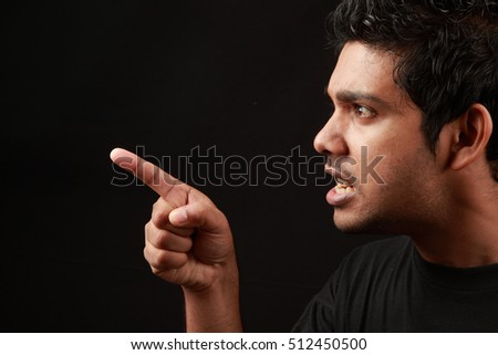 An angry man points his finger in a dark background