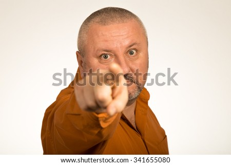 An angry man with beard pointing finger at you - stock photo