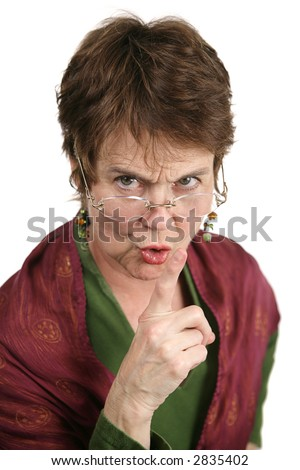 An angry middle aged librarian putting her finger to her lips to tell you to be quiet.  Isolated on white