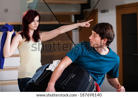 An angry wife asking her husband to move out of their apartment - stock photo