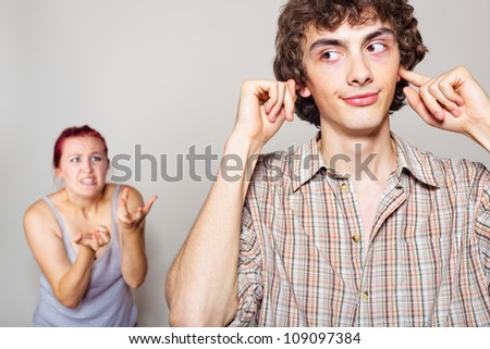 An angry woman yelling at her husband, happy man closed his ears with his hands - stock photo