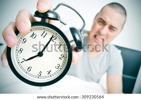 an angry young caucasian man in bed holds in his hand his alarm clock set at seven in the morning - stock photo