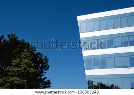 An angular, windowed building next to a tree. - stock photo