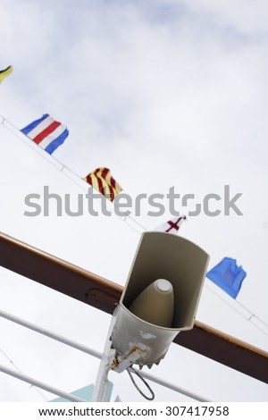 An announcement speaker on a cruise ship with flags and sky in the background.
