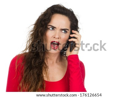 An annoyed and angry woman talking on the phone and looking unhappy. Isolated on white. - stock photo