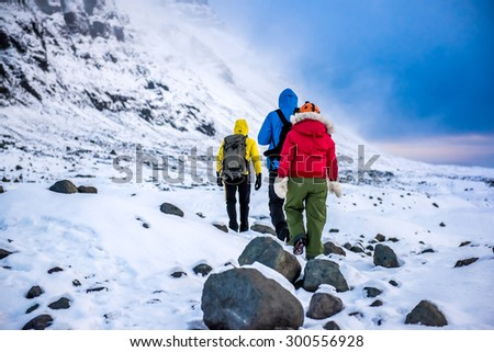 An anonymous group of climbers in snow mountains. - stock photo