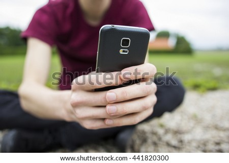 An anonymous young man sitting in front of a field, holding his mobile phone. A concept about loneliness within social media. The focus of the picture is right on the top corner of the phone. - stock photo