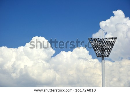 An antenna reaching high into the fluffy white clouds in the blue sky. - stock photo