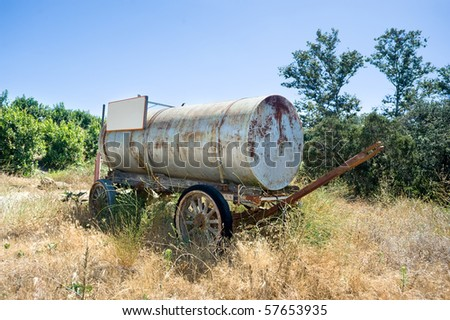An antiquated horse drawn water cart in a rural area during the daytime.