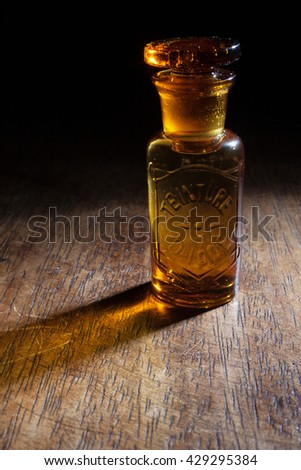 """An antique and vintage glass bottle for pharmaceutical use of """"Teinture d'iode"""" (means Tincture of iodine), that is an antiseptic medicine, isolated on a wooden background. - stock photo"""