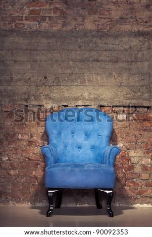 An antique blue velvet chair near the grungy brick wall - stock photo
