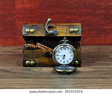 An antique box with a pocket watch. - stock photo