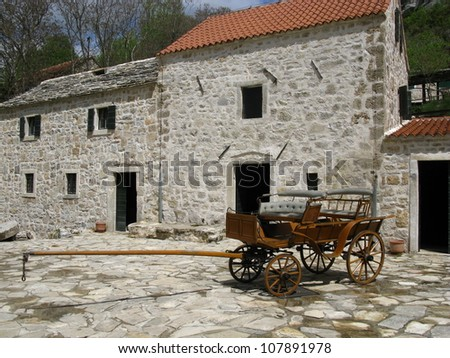 An antique coach in front of a historic house - stock photo