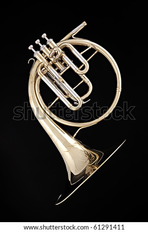 An antique gold French horn isolated against a black background. - stock photo