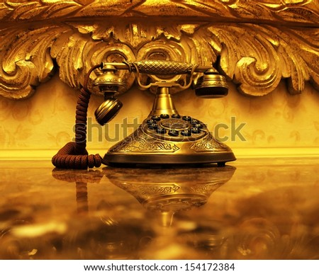 An antique gold telephone and reflection on a shiny marble desktop with vintage style wallpaper and picture frame in the background. - stock photo