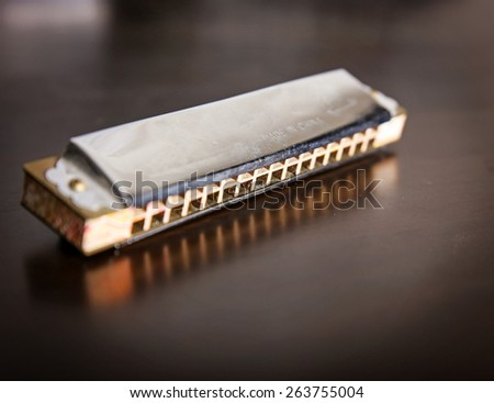 an antique harmonica on a wooden table - stock photo