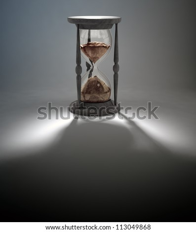 An antique hourglass casting a long shadow - stock photo
