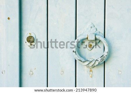 An antique knocker on a wooden door - stock photo