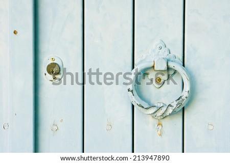 An antique knocker on a wooden door - stock photo